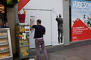 An ice cream seller adjusts a cones dispenser near a Vodafone poster.