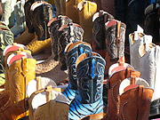 The sun shines brightly on boots displayed at the flea market.