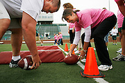 Coach Kevin Lightner shows Sherri Crabtree how to snap a football during the Mom's Weekend football clinic hosted by the OU football team May 5, 2007 at Peden Stadium.