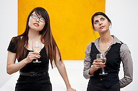 Front view of young females with wine glass looking up in museum