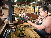 30 APRIL 2015 - TAMPA, FLORIDA, USA: A cigar roller at work in Tabanero Cigars, a cigar factory and coffee house in the Ybor City section of Tampa, FL. Tabanero Cigars handrolls cigars in the traditional Cuban style. Most of the rollers at Tabanero have immigrated to the US from Cuba. Ybor is a historically Cuban immigrant community that has been redeveloped and gentrified into a popular tourist destination lined with cigar factories, boutiques and cafes.     PHOTO BY JACK KURTZ