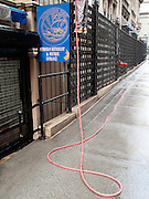 The legs of a worker outside the Petrossian Restaurant in Midtown Manhattan appear at the top of the frame as a red water hose snakes down and accross the pavement.