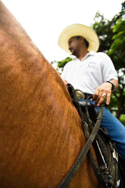 A Costa Rican cowboy sits on top of his horse.