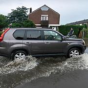 Foto: David Rozing Nederland Barendrecht 29 mei 2018 Wateroverlast door enorme hoosbuien clusterbui clusterbuien hoosbui. Auto rijdt door ondergelopen straten. Code Oranje