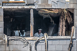 """© Licensed to London News Pictures. 07/08/2018. London, UK. A fire investigator at work at the scene of a house fire in Deptford, east London, in which a 7 year-old boy has died. Six fire engines were called to a """"suspicious"""" fire in the early hours of Tuesday morning. Photo credit: Rob Pinney/LNP"""