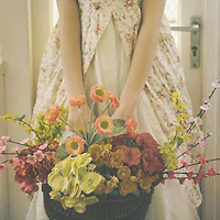 Female youth wearing summer dress facing camera holding a basket full of flowers