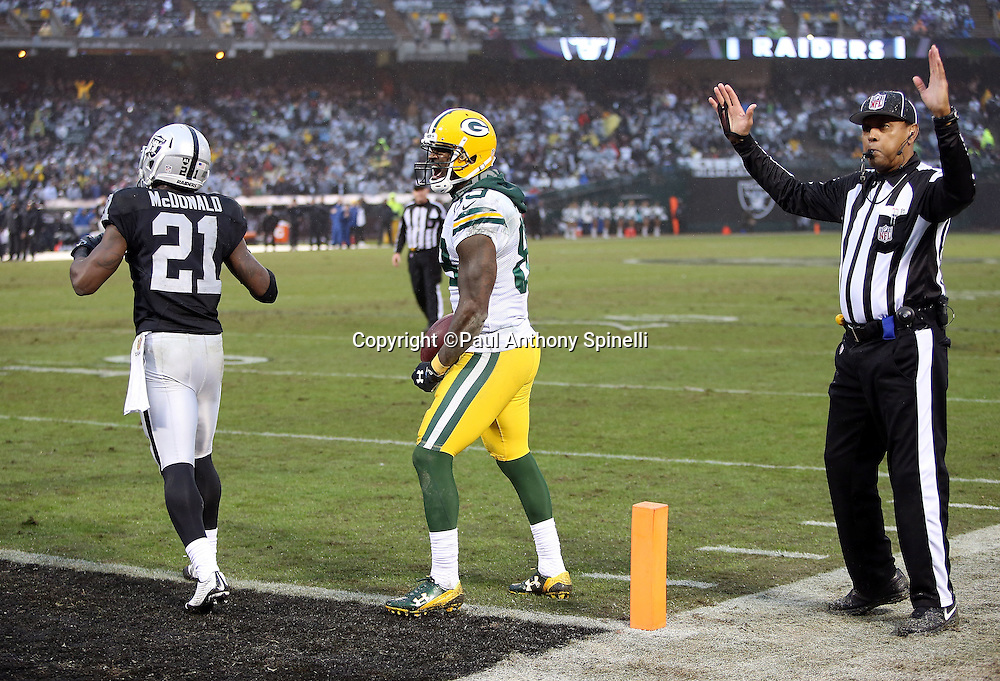 An official signals touchdown while Green Bay Packers wide receiver James Jones (89) yells out in celebration after catching a fourth quarter pass for a touchdown negated by an offensive pass interference penalty while covered by covered by Oakland Raiders cornerback Dexter McDonald (21) during the 2015 week 15 regular season NFL football game against the Oakland Raiders on Sunday, Dec. 20, 2015 in Oakland, Calif. The Packers won the game 30-20. (©Paul Anthony Spinelli)