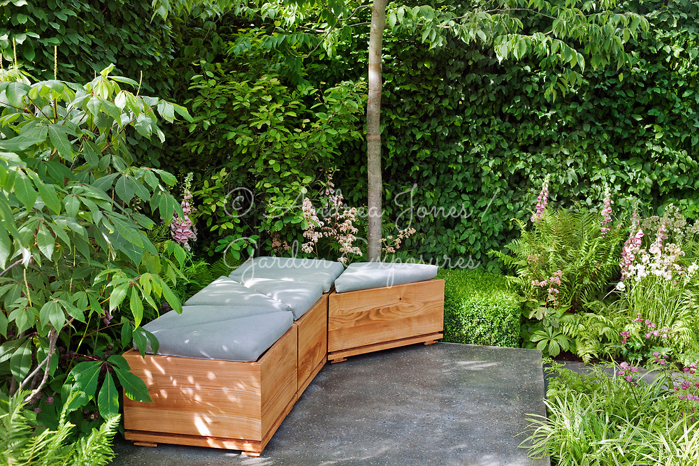The Lands' End Across the Pond Garden by Adam Frost. Wooden bench seat on patio surrounded by hornbeam hedge and perennial borders.