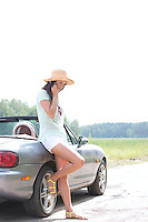 Full-length of woman using cell phone while leaning on convertible at countryside