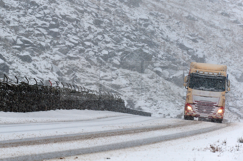 © Licensed to London News Pictures. 23/01/2019. Snowdonia, Conwy, Wales, UK. A truck negotiates the A5 road in Snowdonia National Park, this morning in a heavy snow shower. Snow showers continued throughout last night in Snowdonia. credit: Graham M. Lawrence/LNP