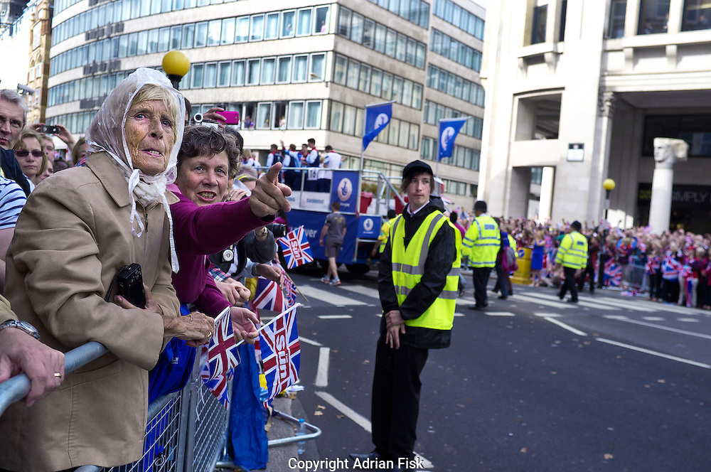 Spectators cheer the British Olympic and paralympic athletes as they pass through London during the victory parade