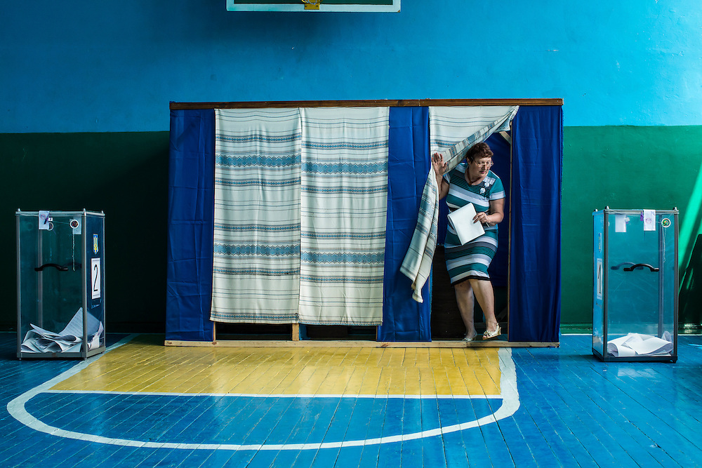 ULYANOVKA, UKRAINE - MAY 25: A woman at a polling station emerges from a voting booth after filling out her ballot in Ukraine's presidential election on May 25, 2014 in Ulyanovka, Ukraine. The elections are widely viewed as crucial to taming instability in the eastern part of the country. (Photo by Brendan Hoffman/Getty Images) *** Local Caption ***