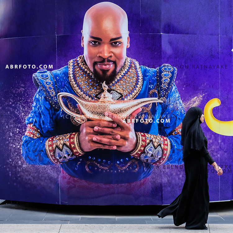 A muslim women in a black Hijab walks past a poster with Michael James Scott playing genie for the theatre production of Aladdin