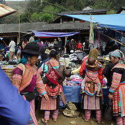 Visitors shopping at the Lung Khau Nhin Market. Vietnam. Lung Khau Nhin Market is rural tribal market hiding itself amongst the mountains and forests of the far north Vietnam about 10 km from the border with China. The market plays an important role for the local ethnic people, Flower Hmong, Black Zao, Zay, and very small ethnic groups  Pa Zi, Tou Zi, Tou Lao. Tourist trips to the market run from Sapa and Lao Cai every week. Lung Khau Nhin Market, Vietnam.15th March 2012. Photo Tim Clayton