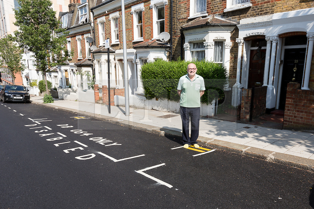 """© Licensed to London News Pictures. 09/07/2015. London, UK. Local resident, Steven Taylor stands by newly painted minature double yellow lines in Mossbury Road, Clapham Junction. The new tiny double yellow lines, measure approximately one foot in length and appeared after Wandsworth Council resurfaced and painted the road. There are two identical sets either side of a disabled parking bay. Owner of one of the properties behind the new road markings, Steven Taylor (not pictured) says """"They're so funny, what on earth could you park in there? They're not even big enough for a bike."""" Photo credit : Vickie Flores/LNP"""