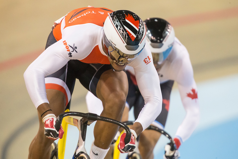 Njisane Phillip (L) of Trinidad and Tobago passes<br /> Joseph Veloce of Canada off the final bend during the men's cycling sprint quarterfinals at the 2015 Pan American Games in Toronto, Canada, July 17,  2015.  AFP PHOTO/GEOFF ROBINS