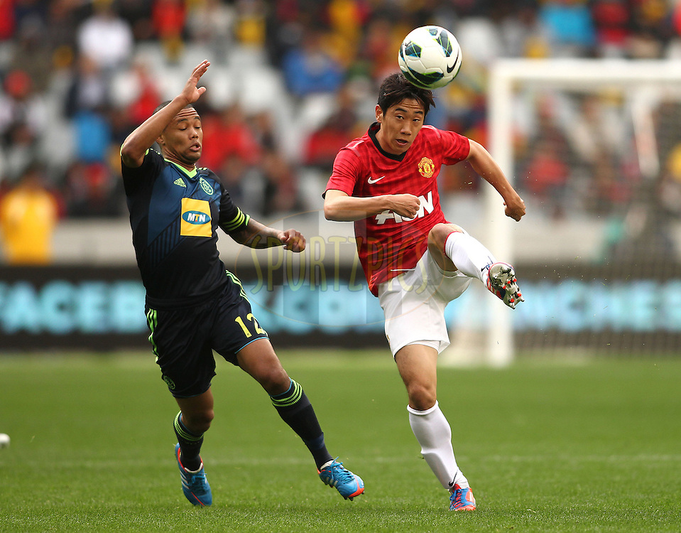 Shinji Kagawa of Manchester United attempts to control the ball ahead of Ajax Cape Town captain Granwald Scott during the Football Invitational 2012 match between Ajax Cape Town and Manchester United held at Cape Town Stadium on 21 July 2012 in Cape Town, South Africa..Photo by Shaun Roy / Sportzpics