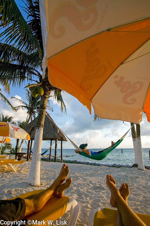(MR) Freinds relax on a beach under coconut palms on the Isla Mueres, Mexico.