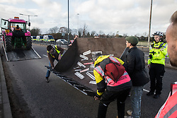 London, UK. 8 December, 2019. Climate activists from Extinction Rebellion arrive with a full-scale mock-up of a bulldozer outside Heathrow airport for a Bikes Against Bulldozers protest against Heathrow expansion and the greenwashing of climate commitments by political parties. The protest took the form of a Critical Mass bicycle ride from Hyde Park followed by a lie-in in front of the bulldozer to which Boris Johnson and John McDonnell were invited in order to fulfil their pledge of lying down in front of bulldozers to be used for Heathrow expansion.
