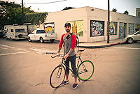 Man with bicycle looks to camera.