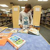 Natalie Walker, 10, takes a few minute to look through a book she plans on checking out Thursday from the Lee County Library.