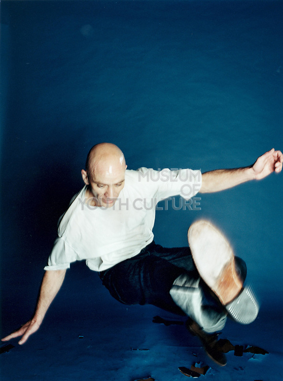 Young man doing a break dance move against blue background.