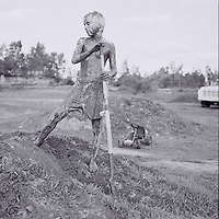 boy digging dirt jumps covered in mud and holding a shovel in shorts and no shirt taken by photographer heather van gaale