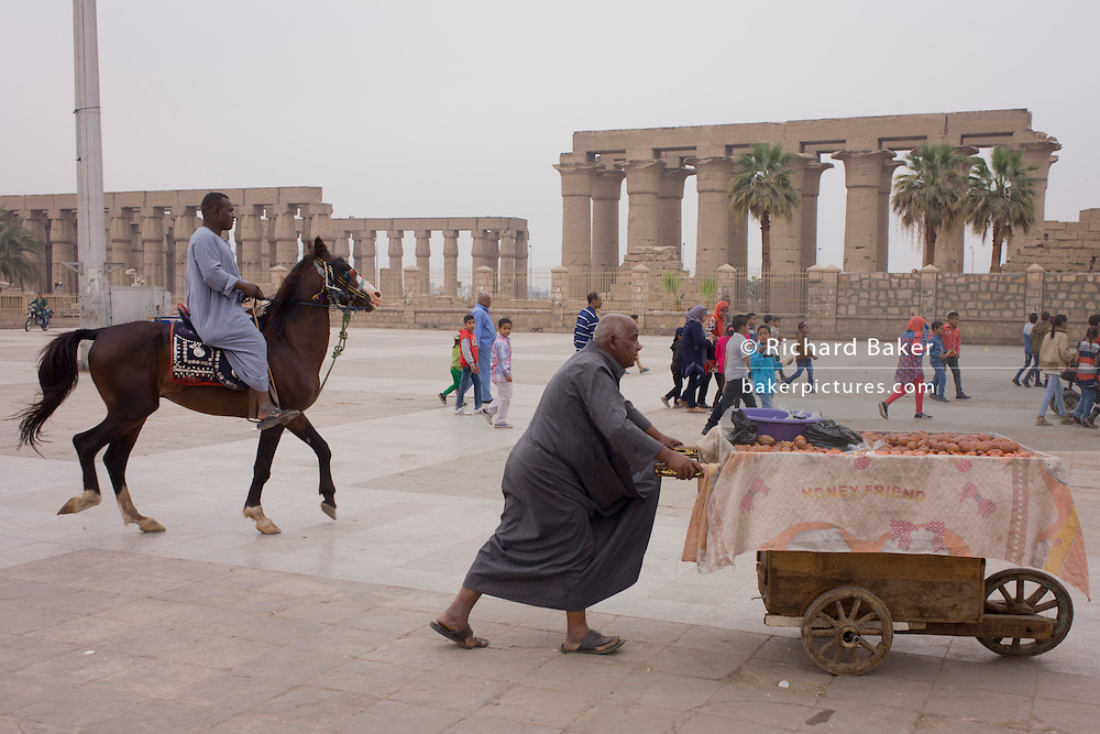 A mounted horse and tourist stallholder in front of the ancient Egyptian columns of Luxor Temple, Luxor, Nile Valley, Egypt. The temple behind was built by Amenhotep III, completed by Tutankhamun then added to by Rameses II. Towards the rear is a granite shrine dedicated to Alexander the Great and in another part, was a Roman encampment. The temple has been in almost continuous use as a place of worship right up to the present day.