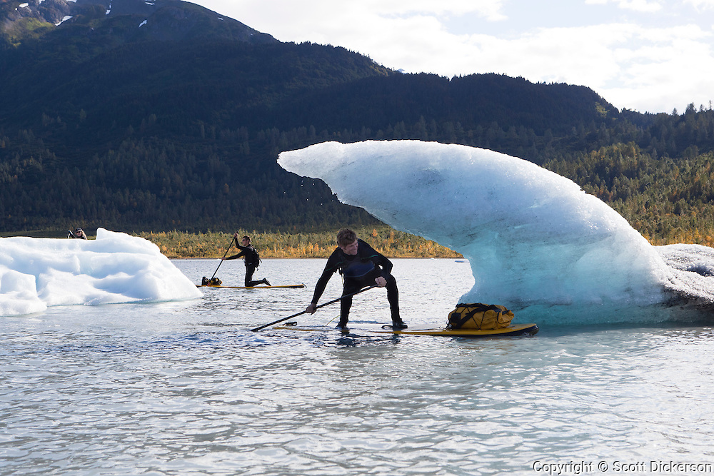 Jeff Hoke pretending to surf his inflatable stand up paddleboard under the lip of a breaking wave. The shape is formed from an iceberg that calved from the Spencer Glacier in Alaska. The Spencer Glacier and Spencer lake are accessed by riding a train into the Kenai Mountains.