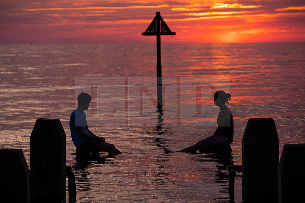 ©Licensed to London News Pictures. 04/07/2019. Aberystwyth, UK. A young couple are silhouetted against the sky as they balance on the wooden jetty in the flat calm sea and watch the glorious sunset in Aberystwyth on the Cardigan Bay coast, west Wales. Photo credit: Keith Morris//LNP
