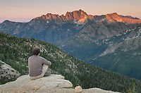 Adult male sitting at cliffside viewpoint and gazing at view of Silver star Mountain on ridge above Cutthroat Pass, near Pacific Crest trail. North Cascades Washington