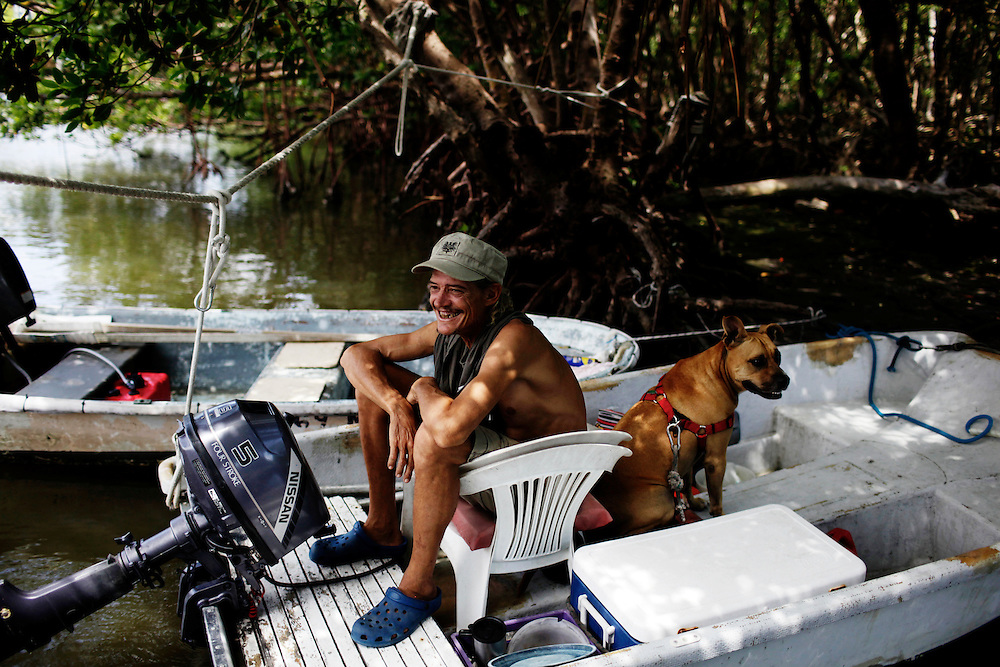 At their landing behind a grocery store on Fort Myers Beach, Scot Janikula and his dog Renegade hang in the shade while running errands. Getting to shore takes more than a few minutes, so most like to stay on their houseboat if they don't have to make the trip.