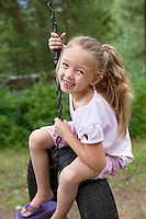 Portrait of young swinging on tire