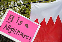 "© licensed to London News Pictures. London, UK 21/04/2012. A placard reading ""F1 is a nightmare"" pictured next to a Bahraini flag as Bahraini exiles and their British supporters protesting outside the headquarters of Formula 1 for Sunday's race to be cancelled. Photo credit: Tolga Akmen/LNP"