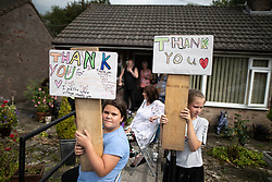 © Licensed to London News Pictures. 03/08/2019. Whaley Bridge, UK. Residents hold up home made placards thanking emergency services for protecting their town . The town of Whaley Bridge in Derbyshire remains evacuated after heavy rain caused damage to a slipway on the Toddbrook Reservoir , threatening homes and businesses with flooding. Photo credit: Joel Goodman/LNP