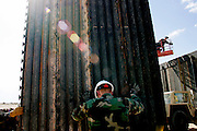Staff Sargeant Jon Bylsma of the 115th Group of the Utah National Guard helps build a new fence along the US-Mexico border near San Luis, AZ on Wednesday, June 7, 2006.<br />
