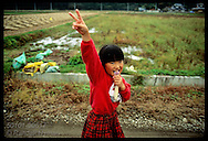 Girl flashes peace symbol, often used on foreign tourists, as she walks by rice paddy; Utsunomiya Japan