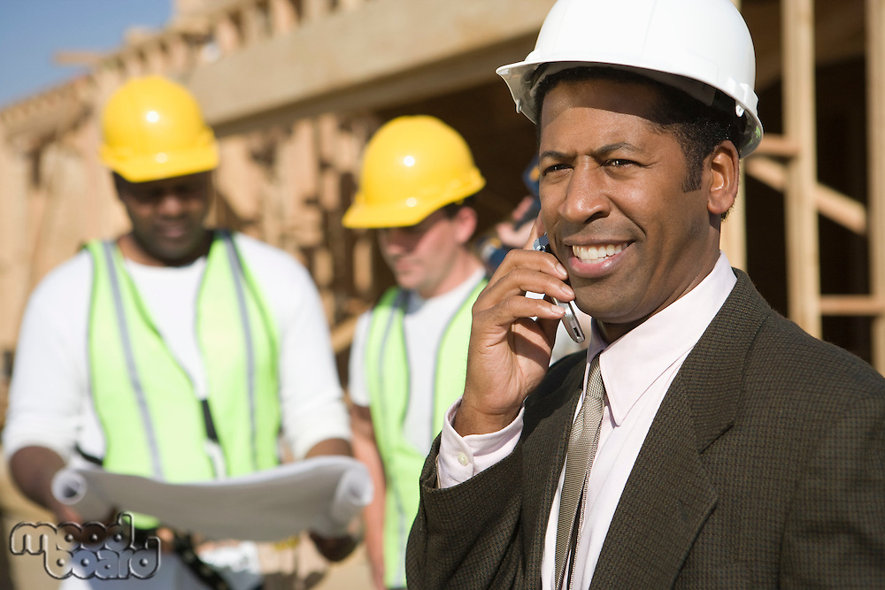 Architect using mobile phone and two construction works looking at blueprints