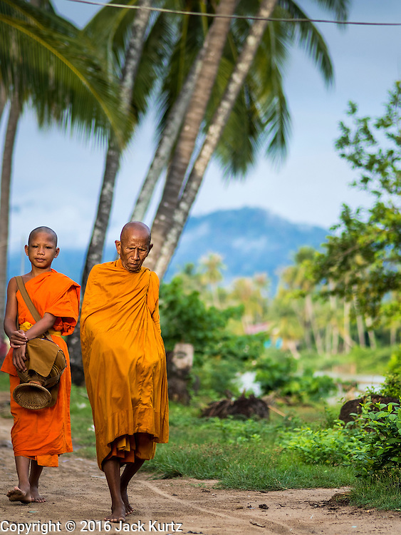 "20 JUNE 2016 - DON KHONE, CHAMPASAK, LAOS: Buddhist monks from Wat Khone Nua on their morning alms' rounds, called the ""tak bat"" in Don Khone village on Don Khone Island. Don Khone Island, one of the larger islands in the 4,000 Islands chain on the Mekong River in southern Laos. The island has become a backpacker hot spot, there are lots of guest houses and small restaurants on the north end of the island.     PHOTO BY JACK KURTZ"