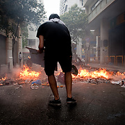 A protester throws cardboard boxes into a burning barricade in Nikis Street near  Syntagma  (Constitution) square, June 29, 2011 cardboard boxes into a burning barricade in Nikis Street near  Syntagma  (Constitution) square, June 29, 2011