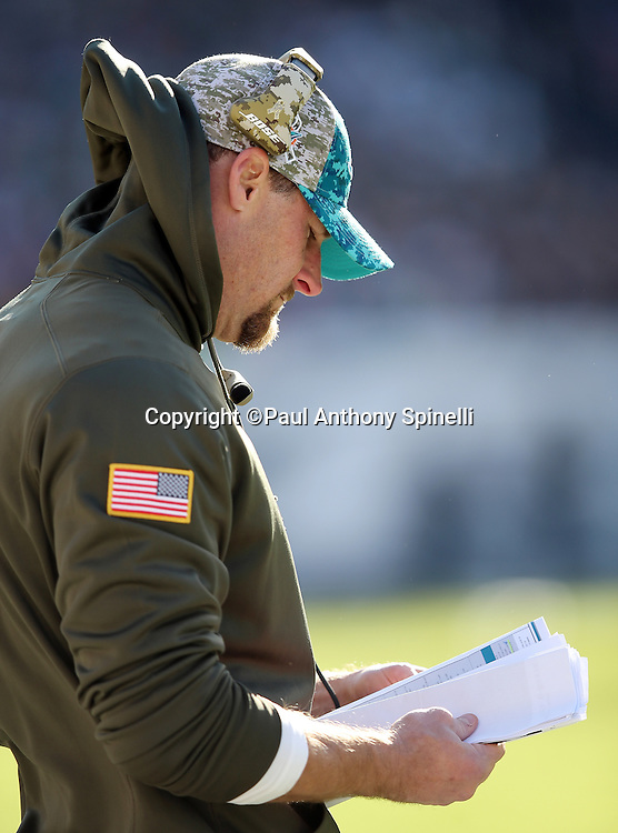 Miami Dolphins head coach Dan Campbell checks out his play chart on the sideline during the 2015 week 10 regular season NFL football game against the Philadelphia Eagles on Sunday, Nov. 15, 2015 in Philadelphia. The Dolphins won the game 20-19. (©Paul Anthony Spinelli)