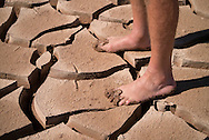 Man's feet stands on cracked mud, Grand Canyon