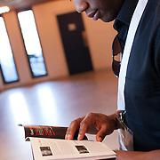 Caustan De Riggs peruses the TEDxWaterloo booklet in the lobby between speaker presentations.
