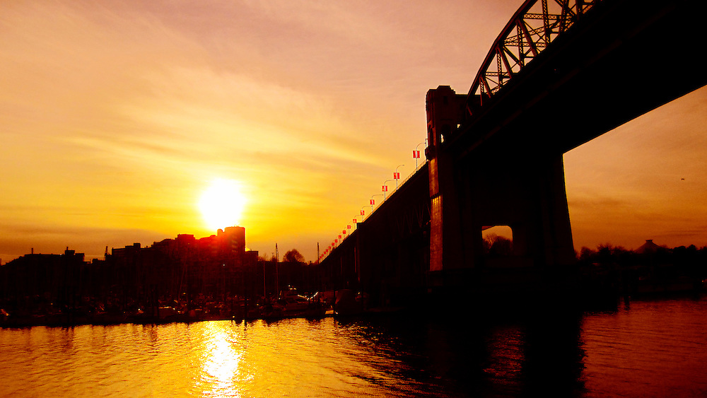 Burrard Bridge looms over False Creek at sunset, red banner flags flapping on the bridge, Vancouver BC