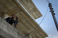 A Free Syrian Army soldier guards the outskirts of the city from a building site outpost. Al Janoudiyah, Syria