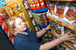 Young woman working in Blockbuster video rental shop; arranging shelves of crisps; Merseyside