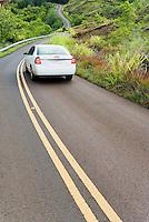 A car driving on a winding highway 550 near Waimea Canyon just North of Waimea, Kauai, Hawaii, USA.