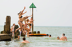 © London News Pictures. 21/06/2017. Aberystwyth, UK. People in Aberystwyth cooling off by diving into the sea on yet another day of clear blue skies and searing heat on the west coast of Wales as the mini heat-wave continues over the British Isles. The Met Office has warned of heavy rain and thunderstorms with the chance of localised flooding affecting much of the UK in the next 24 hours as the weather system starts to break down after many days of record hight temperatures. Photo credit: Keith Morris/LNP