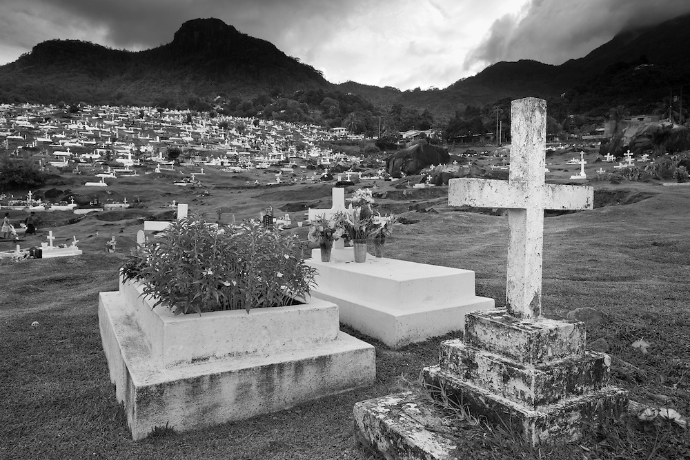 Seychelles, Mahe Island, Victoria, Rows of historic graves at Bel Air Cemetery beneath storm clouds