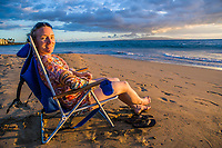A middle aged woman sitting on a beach enjoying the sunset on the pacific ocean in Kihei, Maui, Hawaii, USA.
